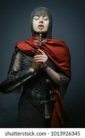 Gorgeous young woman in knight armour holding dagger