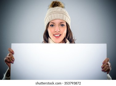 Gorgeous young woman in a knitted winter cap holding a blank white sign or placard in front of her chest with copy space for your text, close up head and shoulders over grey