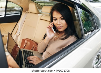 Gorgeous young woman with laptop sitting in car and talking on the phone