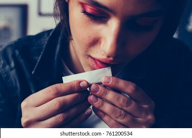 gorgeous young woman licking cigarette paper, preparing to smoke