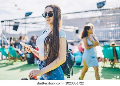 Gorgeous young woman with long brunette hair sending sms message to friend on modern smartphone standing outdoors.Stylish hispter girl in black sunglasses and backpack updating telephone device