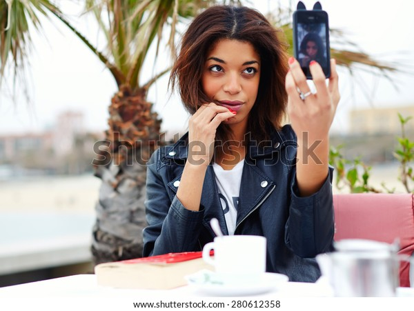 Gorgeous young woman making self portrait with a cell phone camera while enjoying a day out and sitting in coffee shop at her recreation time, female hipster taking a picture of herself on smart phone