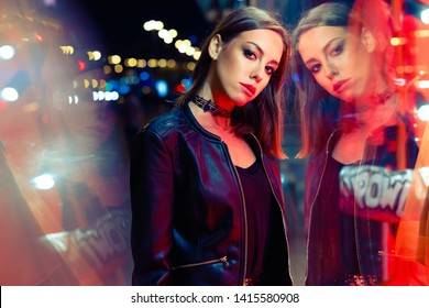 gorgeous young woman posing in leather jacket at night city