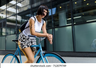 Gorgeous young woman posing on blue colored bicycle next to modern building