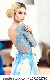 Gorgeous young woman posing in restaurant dressed in evening or wedding chic gown. Beauty, fashion.