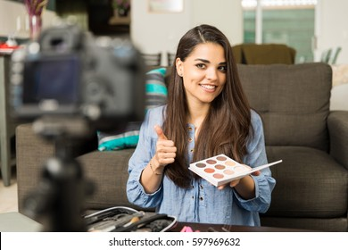 Gorgeous young woman reviewing and endorsing cosmetic products for her beauty video blog at home
