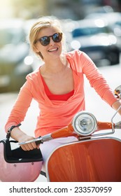 gorgeous young woman riding  a vintage scooter in the street, she has a topknot, sunglasses and a pink helmet