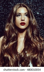 Gorgeous young woman with sensual red lips and stunning long hair. Eyelash extensions, false eyelashes.