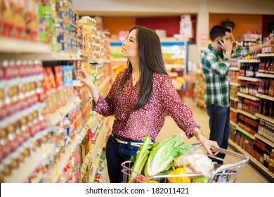 Gorgeous young woman with a shopping cart looking at some products on a supermarket aisle
