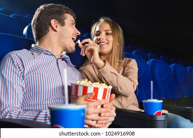 Gorgeous young woman smiling feeding her boyfriend with popcron enjoying date at the cinema love affection relationships dating lifestyle romance valentines couples entertainment leisure.
