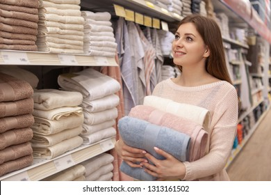 Gorgeous young woman smiling happily, shopping at textile department of a local supermarket. Beautiful female customer buying cotton towels at home goods store, copy space