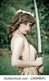 Gorgeous young woman striking a stance holding a sword in her hands while performing in the park