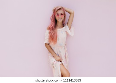 Gorgeous young woman in summer clothes posing with shy smile. Indoor photo of lovable caucasian girl with pink hair isolated on light background.