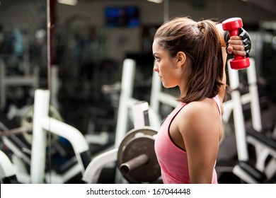 Gorgeous young woman using dumbbells to work on her triceps. Lots of copy space