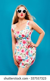 Gorgeous young woman, wearing in white dress with floral pattern, and sunglasses, posing on blue background, in studio, waist up