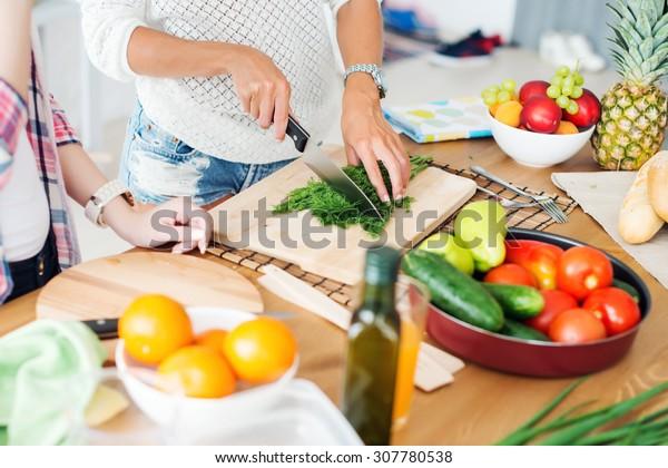 Herrliche junge Frauen bereiten das Abendessen in einer Küche Konzept Kochen, kulinarische, gesunde Lebensweise