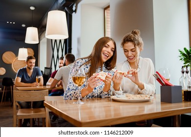 Gorgeous young women sitting in restaurant and having fun. Two best friends eating appetizing pizza and drinking delicious white wine. Girls smiling, looking at camera and posing.