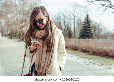Gorgeus woman in stylish beige coat using a smartphone outdoors
