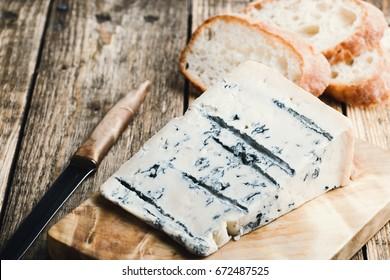 Gorgonzola cheese with ciabatta bread on rustic wooden cutting board