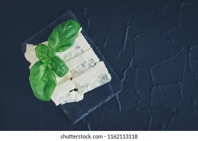 Gorgonzola cheese with mascarpone with basil on slate plate on dark background with place for text. Tasty appetizers. Top view. Copy space.