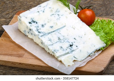 Gorgonzola cheese in wood background with salad leaves and tomato
