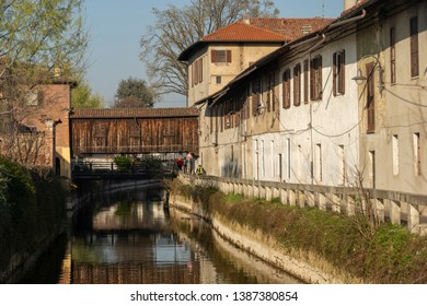 Gorgonzola, Italy - March 23, 2019: Gorgonzola (Milan, Lombardy, Italy): old houses along the Martesana canal, with wooden bridge and bicycle lane