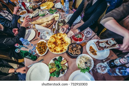 Gori, Georgia - April 23, 2015. Tourists sitting at the restaurant table full fo Georgian traditional food
