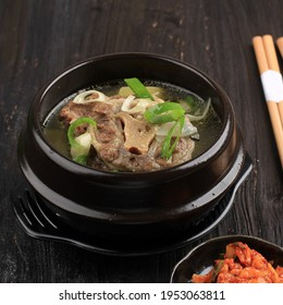 Gori Gomtang (Sokkori Gomtang) or Korean Beef Oxtail Stew  Soup, Served in the Black Korean Bowl with Kimchi and Sliced Green Onion