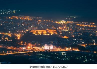 Gori, Shida Kartli Region, Georgia. Gori Fortress In Cityscape In Night Illumination. Travel Destination In Night Lights. Goris Tsikhe Is A Medieval Citadel.
