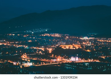 Gori, Shida Kartli Region, Georgia. Gori Fortress In Cityscape In Evening Illumination Under Blue Sky. Travel Destination In Night Lights. Goris Tsikhe Is A Medieval Citadel