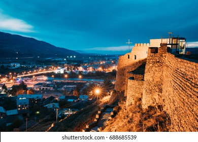 Gori, Shida Kartli Region, Georgia. Walls Of Gori Fortress And Cityscape In Evening Illumination Under Blue Sky. Travel Destination In Night Lights. Goris Tsikhe Is A Medieval Citadel