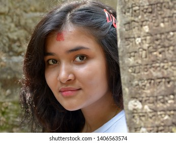 GORKHA, NEPAL - MAY 11, 2019: Young Nepali woman with beautiful hair and red tilaka mark on her forehead peeks around a stone pillar inside the Gorkha temple, on May 11, 2019.