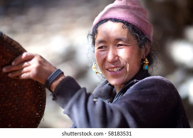 GORKHA, NEPAL - NOVEMBER 28, 2009: Gurung woman with basket working in the fields