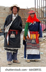 GORKHA, NEPAL - SEPTEMBER 24: woman and the man in a traditional Tibetan attire, stand near the house on September 24, 2010 in Gorkha District, Manaslu Area, Nepal