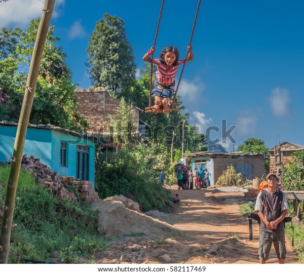 From Gorkha village to Arughat Bazar village, on Manaslu Circuit trail-September 30, 2009: Teenage girls swinging bravely on a quite high improvised swing, Gorkha district, Nepal