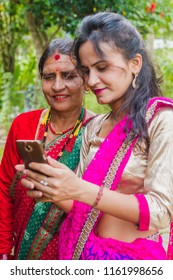 Gorkha,Nepal - Sep 30,2017: Beautiful Nepali Girl showing photo after taking selfie with her smartphone in the rural village of Nepal.