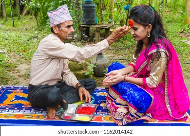 Gorkha,Nepal - Sep 30,2017: A Girl Receiving Tika and blessings From Her Father at Dashain Festival in the village of Nepal.