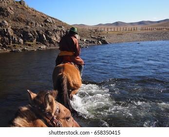 Gorkhi Terelj National Park, Mongolia - 01 October, 2016: Mongolian herder crossing a river on horseback