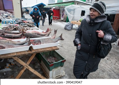 Gorlovka Donetsk, Ukraine - January 15, 2013: The central city market in the open air. An elderly woman buying products on the market.