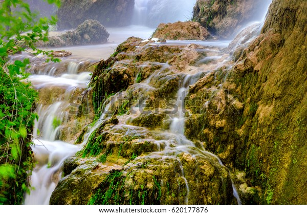 Gorman Falls, at Colorado Bend State Park, in the Texas Hill Country flows peacefully down a cascade of rocks covered in rich green moss.