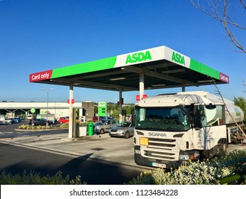 Gorseinon, UK: June 27, 2018: A self-service petrol station at an Asda supermarket. A Scania delivery truck is off-loading its fuel to the underground storage tanks. Asda is owned by Wal-mart.