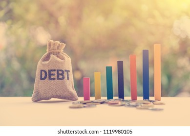 Gorvernment or public / national debt concept : Color wood bar graph, coin and a debt bag on a table, depicts the government collects taxes less than spending, the difference is called deficit or debt