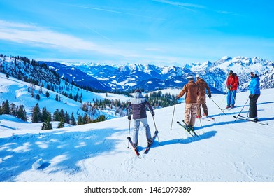 GOSAU, AUSTRIA - FEBRUARY 26, 2019: The group of skiers starts the downhill from top of Zwieselalm mountain, surrounded by snowbound peaks of Dachstein West massif of Alps, on February 26 in Gosau.