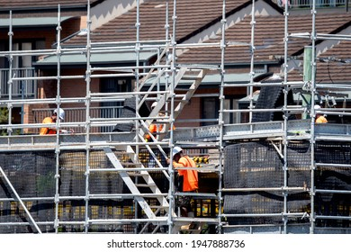 Gosford, Australia. March 1, 2021. Worker assembling scaffolding on new social housing home unit block at 56-58 Beane St. Part of a building construction series.