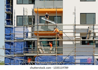 Gosford, New South Wales, Australia - March 4, 2019: Workers disassembling scaffolding and removing safety netting on new home units building site at 47 Beane St.  Building progress Update 194