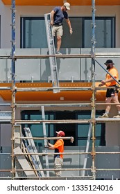 Gosford, New South Wales, Australia - March 4, 2019: Workmen close up, dismantling  scaffolding and removing safety netting on new home units building site at 47 Beane St. Construction update 195