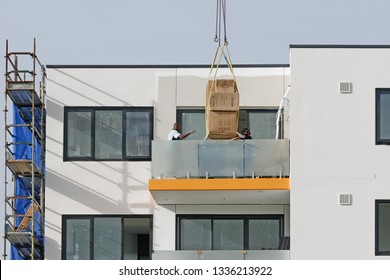 Gosford, New South Wales, Australia - March 6, 2019:  A working tower crane delivering materials,  to installers on new home units building site at 47 Beane St.
