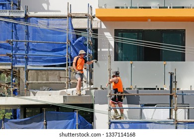 Gosford, New South Wales, Australia - March 6, 2019: Workmen close up, dismantling scaffolding and removing safety netting on new home units building site at 47 Beane St. Construction update 205.