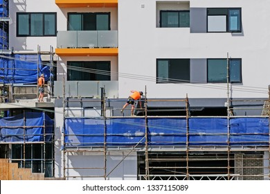Gosford, New South Wales, Australia - March 6, 2019: Workmen dismantling scaffolding and removing safety netting on new home units building site at 47 Beane St. Construction update 206.