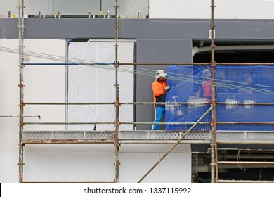 Gosford, New South Wales, Australia - March 6, 2019: Workmen close up, dismantling scaffolding and removing safety netting on new home units building site at 47 Beane St. Construction update 207.